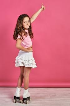 Colpo verticale di una bambina in pattini a rotelle in posa e gesticolando il segno simile