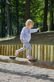 Vertical shot of a little girl walking on a wooden tube in the playground