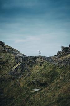 Ripresa verticale di una persona sola in piedi in cima a una scogliera