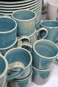 Colpo verticale di molte tazze e piatti in ceramica blu