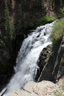 Vertical shot of a low waterfall with white foam in the forest with cliffs and greenery