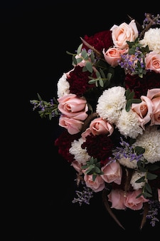 Vertical shot of a luxurious bouquet of pink and red roses and white dahlias on a black background
