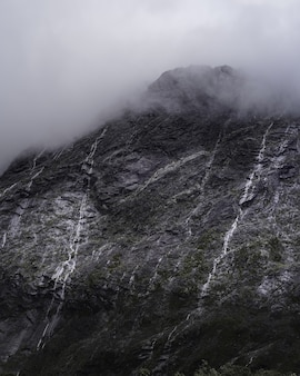 Vertical shot of a majestic mountain with small waterfalls in a foggy weather
