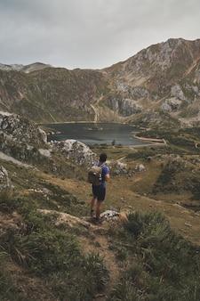 Ripresa verticale di un viaggiatore con zaino e sacco a pelo maschio che guarda un bellissimo lago nel parco naturale di somiedo in spagna