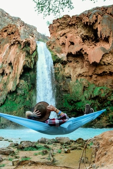 Vertical shot of a male lying on a hammock beside a waterfall flowing down from a hill