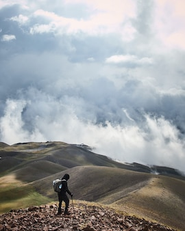 Vertical shot of a male standing on a mountain with a cloudy sky in the background
