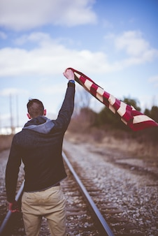 Vertical shot of a male standing on train tracks while holding up the united states flag