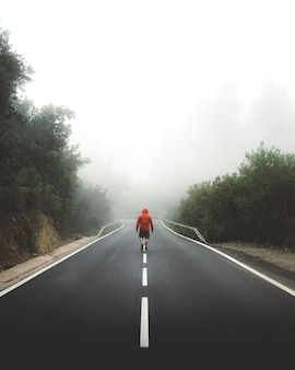 Vertical shot of a male walking through the highway covered by fog