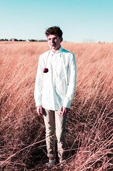 Colpo verticale di un maschio che indossa una camicia bianca con una rosa in bocca Foto Gratuite