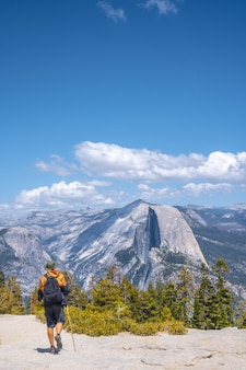 Vertical shot of a man hiking in the yosemite national park, sentinel dome yosemite the usa