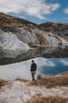 Vertical shot of a man walking near blue lake walk in new zealand surrounded by mountains