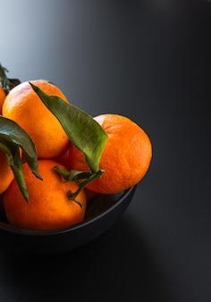 Colpo verticale di mandarini con foglie verdi su fondo nero