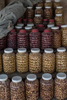 Colpo verticale di molte bottiglie di plastica con coperchi bianchi pieni di vari piccoli raccolti
