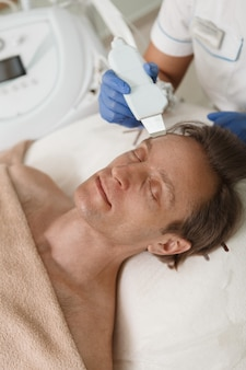 Vertical shot of a mature man getting ultrasound skin cleanse by beautician
