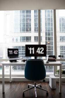 Vertical shot of a modern office desk with flat-screen monitors showing the time