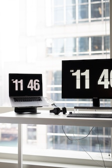 Vertical shot of a modern office desk with monitors showing the time and headphones