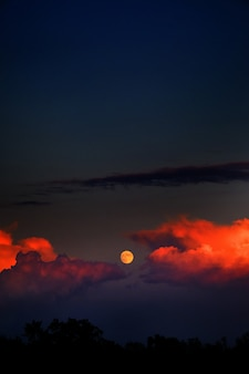 Vertical shot of the moon and fire clouds in the dark sky
