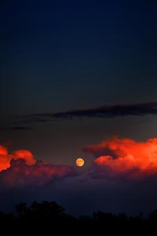 Colpo verticale della luna e nuvole di fuoco nel cielo scuro