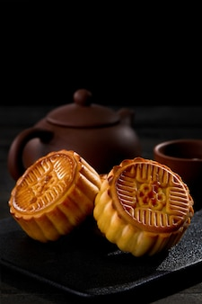 Vertical shot of mooncakes with a cup of tea on a black surface