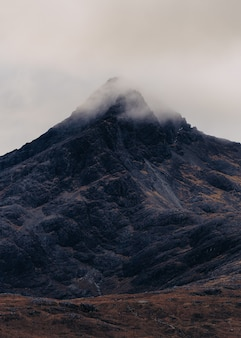 Vertical shot of a mountain covered in a cloud of fog in scotland, isle of skye