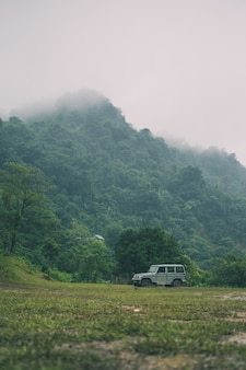 Vertical shot of mountains covered in greenery and a car