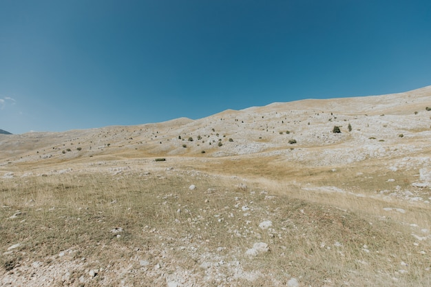 Colpo verticale di montagne e colline con molte rocce sotto il bel cielo blu