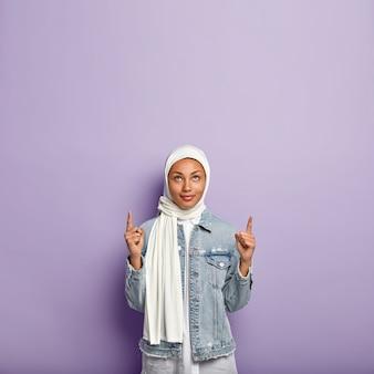 Inquadratura verticale della signora musilm che raggiunge la prima posizione al lavoro, indica sopra, ha un'espressione sicura, indossa una sciarpa bianca e una giacca di jeans