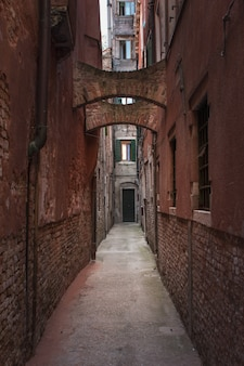 Vertical shot of a narrow alley in venice, italy