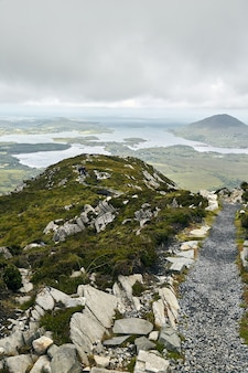 Vertical shot of a narrow pathway in connemara national park in ireland under a cloudy sky