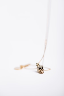 Vertical shot of a necklace with a skull-like charm on white background