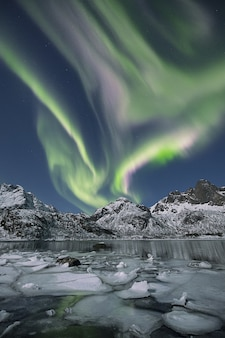 북극광 아래 눈이 덮여 언덕으로 둘러싸인 얼어 붙은 호수의 세로 샷