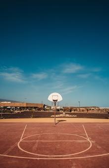 青い空の下にフープが見えるバスケットボールコートの垂直ショット