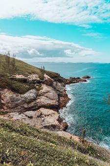 Вертикальный снимок пляжа, покрытого камнями и травой