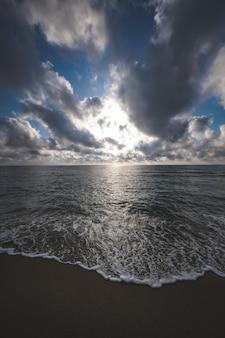 青い曇り空の下で海に囲まれたビーチの垂直ショット