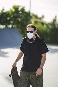 그의 스케이트 보드를 들고 공원에서 산책하는 얼굴 마스크를 쓰고 수염 난 남성의 세로 샷