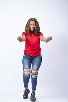 お祝いの気分で、何かにとても幸せを感じている美しいアフリカの女性の垂直ショット