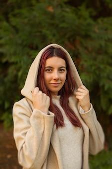 日中の公園でコートを着ている美しい白人の女の子の垂直ショット