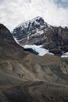 田園地帯の雪に覆われた荒い岩層の上の美しい雲景の垂直ショット