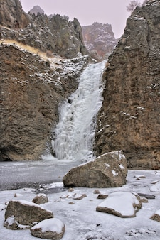 岩の崖の間で美しい凍った滝の垂直ショット
