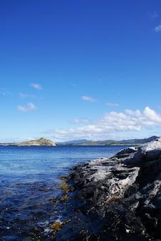 ノルウェーの曇り空の下で崖に囲まれた美しい湖の垂直ショット