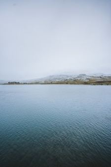 フィンセ、ノルウェーの高い山々に囲まれた美しい湖の垂直ショット