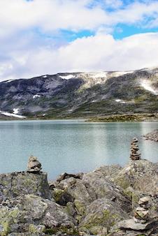 노르웨이의 높은 록키 산맥으로 둘러싸인 아름다운 호수의 세로 샷
