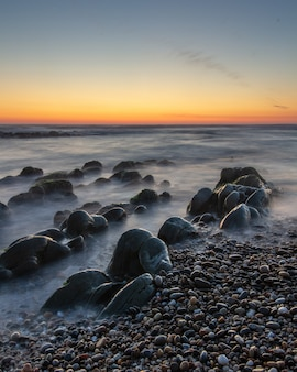 Вертикальный снимок красивого заката на каменистом пляже