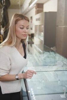 宝石店で買い物をしている美しい女性の垂直ショット