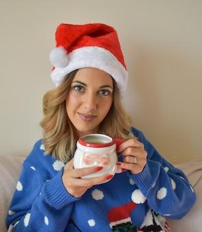クリスマスのドレスとサンタのマグカップを持った帽子をかぶった美しい若い女性の垂直ショット