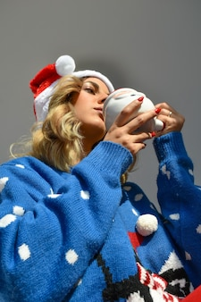 산타 컵을 들고 크리스마스 드레스와 모자를 쓰고 아름다운 젊은 아가씨의 세로 샷