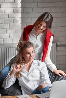 Вертикальный снимок красивой молодой женщины, задумчиво глядя в сторону, делая заметки. лучшая подруга тщательно поправляет прическу. дружба люди отношения сестры одноклассники домашнее задание.