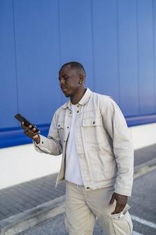 彼の携帯電話を屋外で保持している黒人男性の垂直ショット