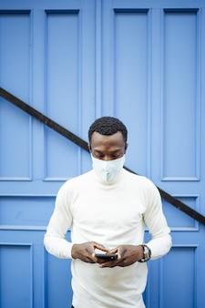 Вертикальный снимок чернокожего мужчины в санитарной маске, смотрящего на свой телефон