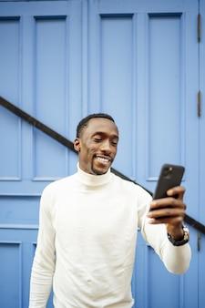 Вертикальный снимок черного мужчины в водолазке, смотрящего на свой телефон